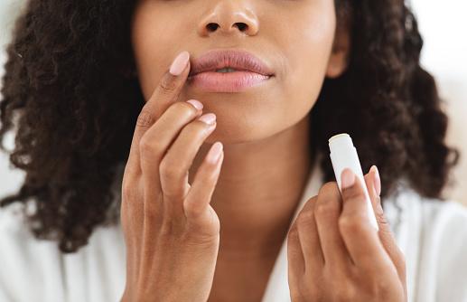 Lip Care. Unrecognizable black woman applying moisturising chapstick on lips, cropped image, closeup