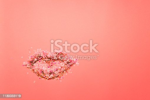 istock Lip Shape Made Of Red, White, Pink Confetti On Textured Coral Colored Paper Background With Space For Text And Design. Pop Art Style. 1130033119