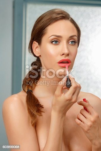 Applying red lipstick - Lip gloss. Beautiful sensual lips. Lips slightly open.  Beauty portrait.  Beautiful  young  woman, Brunette, hair back, ponytail  blue eyes.  Body care in the bathroom.