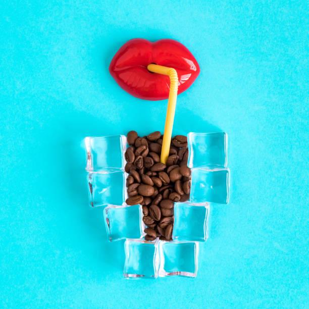 Juguete de labios con paja para beber y taza de café helado hecho de cubitos de hielo y granos de café. - foto de stock