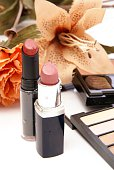 Two moist lipsticks on white with blurred makeup and flowers in the background