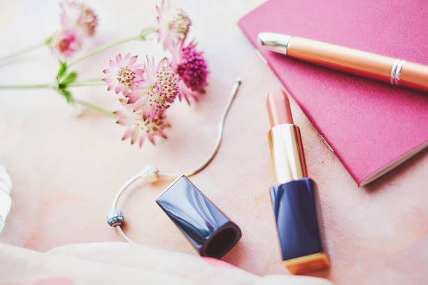 Lipstick and notepad or passport with flowers over a painted background stock photo