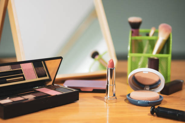 Lipstick and other makeup equipment on dressing table stock photo