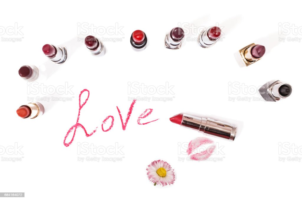 Lipstick isolated on white background. Female lip pencil. Kiss of lips on paper. The word love written in lipstick. Reflection of lipstick in the mirror. View from above. Concept. Decorative cosmetics foto stock royalty-free