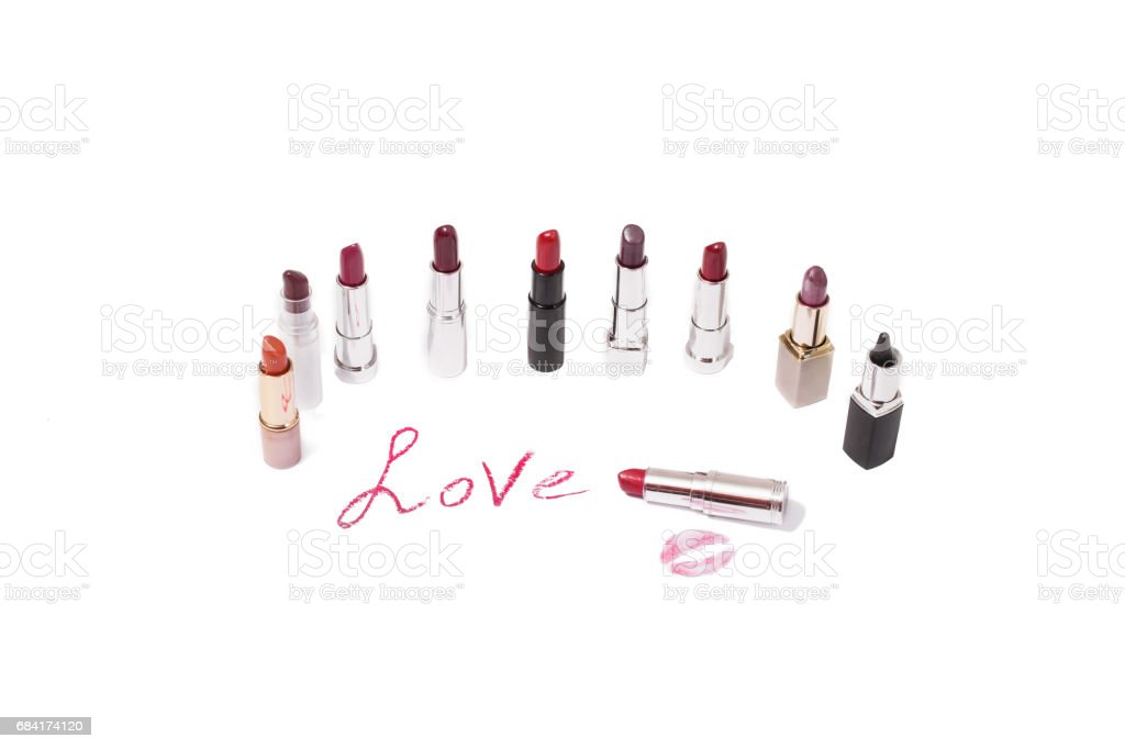Lipstick isolated on white background. Female lip pencil. Kiss of lips on paper. The word love written in lipstick. Reflection of lipstick in the mirror. View from above. Concept. Decorative cosmetics royalty-free stock photo
