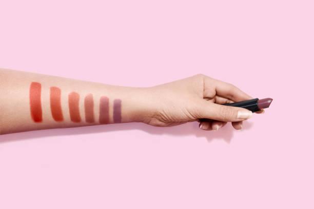 Lipstick makeup swatches on female hand holding lipstick stock photo