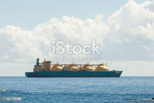 liquefied natural gas LNG transportation tanker ship, blue sea and sunny sky background with copy-space
