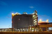 Liquefied natural gas (LNG) storage tank at dusk.