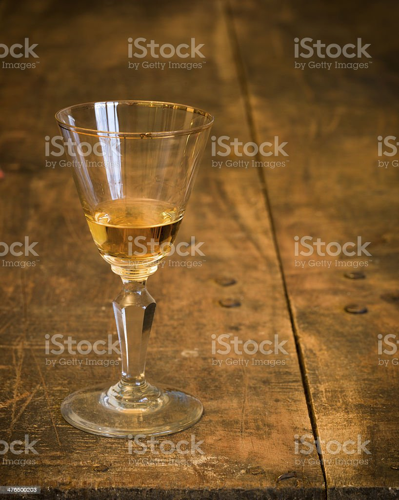 Liqueur - Antique glass on old wooden table. stock photo