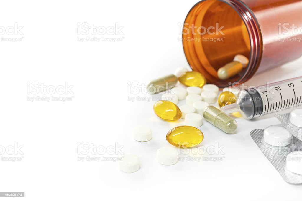 Liquid capsules and pills spilling out of bottle royalty-free stock photo
