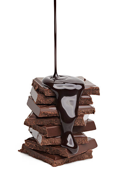 liquid chocolate being poured on a stack of solid chocolate  - chocolate syrup stock photos and pictures