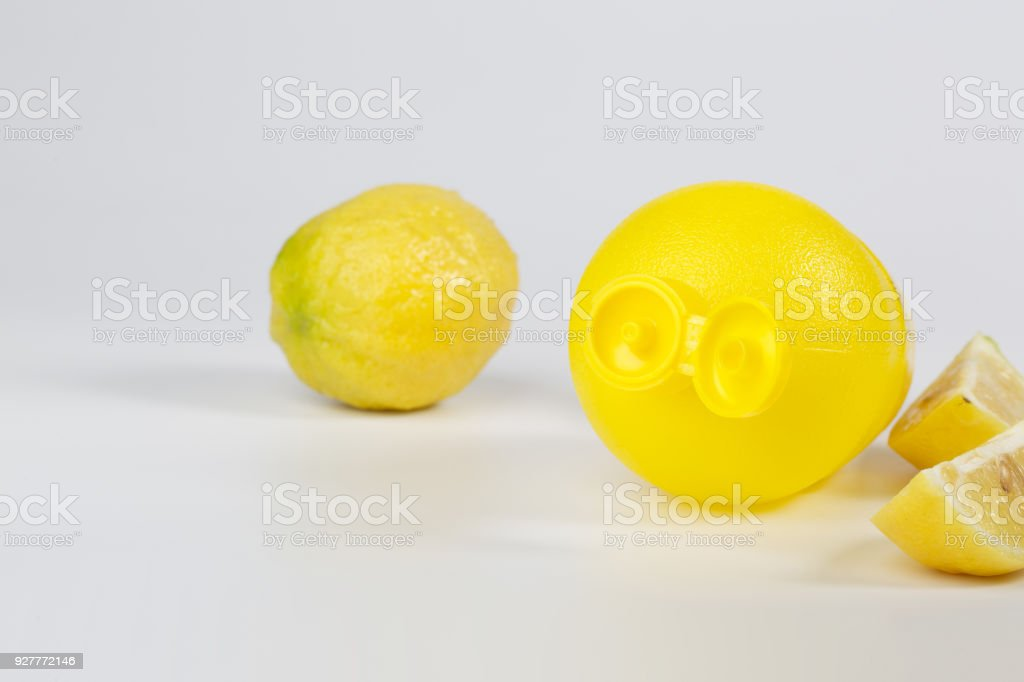 Liquid citric acid in a plastic bottle and pieces of fresh lemon. stock photo