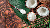 Top view of coconut MCT oil in bowl and in spoon and halved coco-nut on wooden table. Health Benefits of MCT Oil. MCT or medium-chain triglycerides, form of saturated fatty acid. Flat lay. Copy space