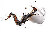 Liquid coffee wave splashing out from a white cup mug, isolated on white background. Clipping path included.