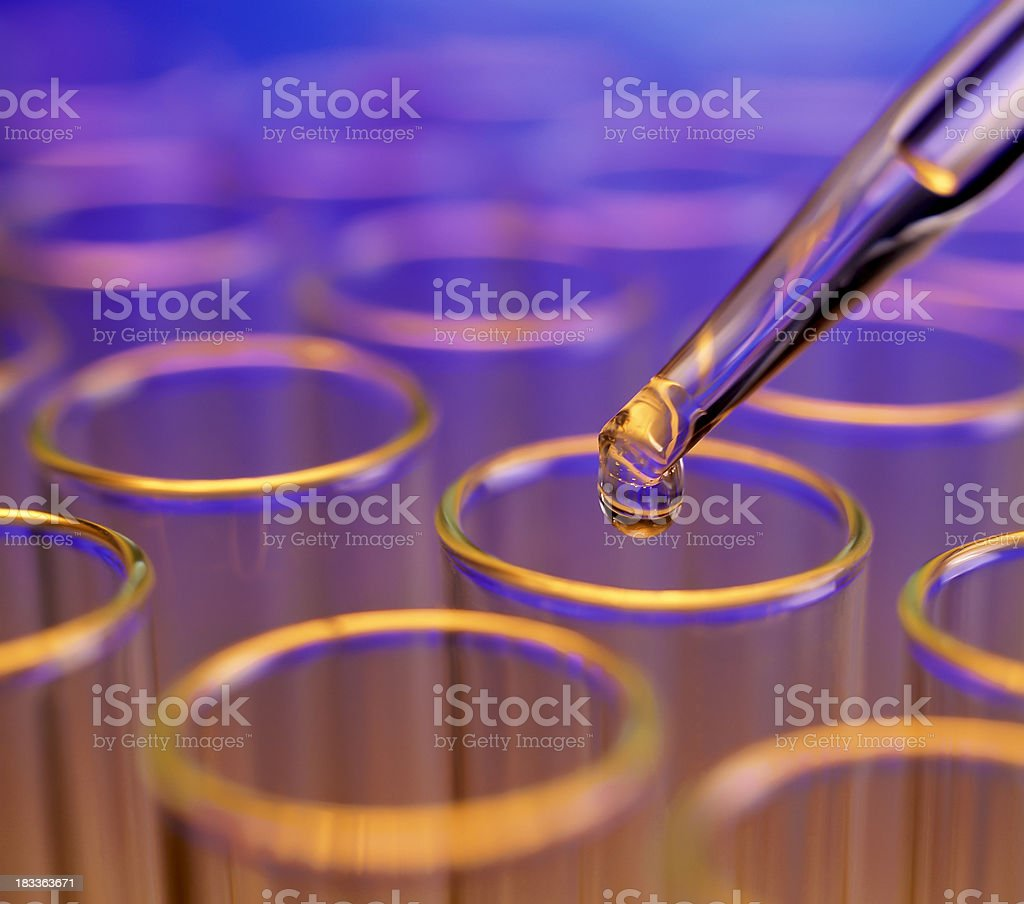 Liquid drop falling into test tubes stock photo