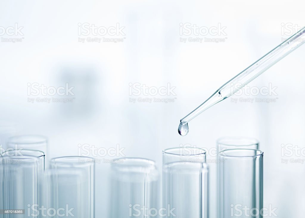 Liquid drop from pipette to test tube stock photo