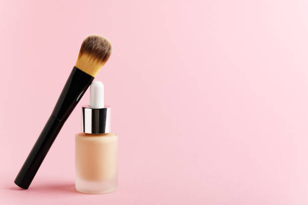 Liquid foundation cream unbranded bottle with makeup brush. Facial correction, liquid concealer, tone, bb, cc cream skincare product on pink background. Feminine cosmetics accessory with copy space stock photo