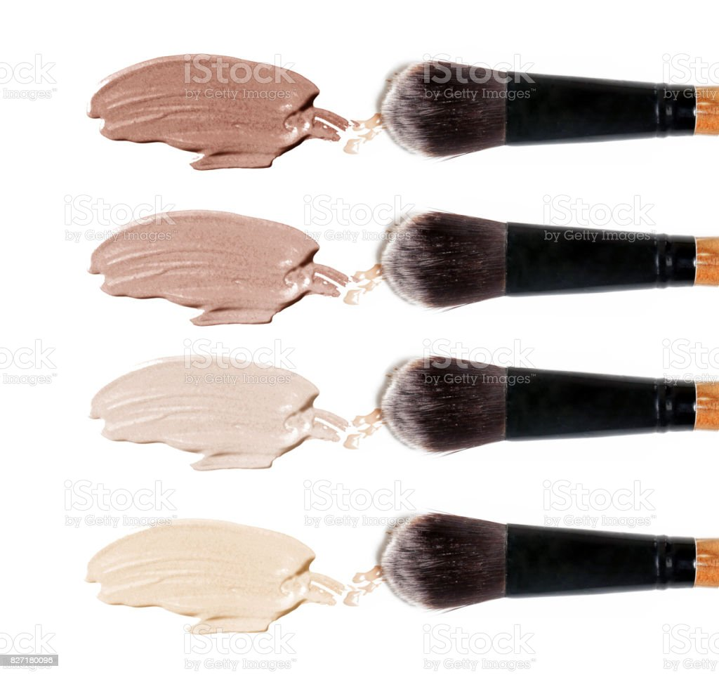 Liquid foundation samples and makeup brushes on white stock photo