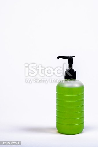 Liquid green hand soap in a transparent bottle sits on a white surface for prevention of the coronavirus.