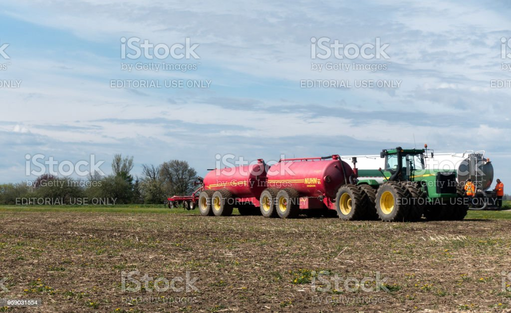 A large John Deere tractor pulling dual liquid manure tanks while...