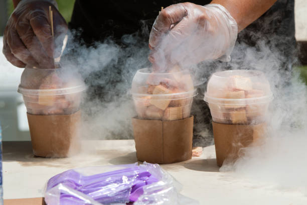 Liquid Nitrogen Steams As Man Prepares Frozen Treats At Festival Man's hands prepare frozen deserts using liquid nitrogen at ice cream festival. liquid nitrogen stock pictures, royalty-free photos & images