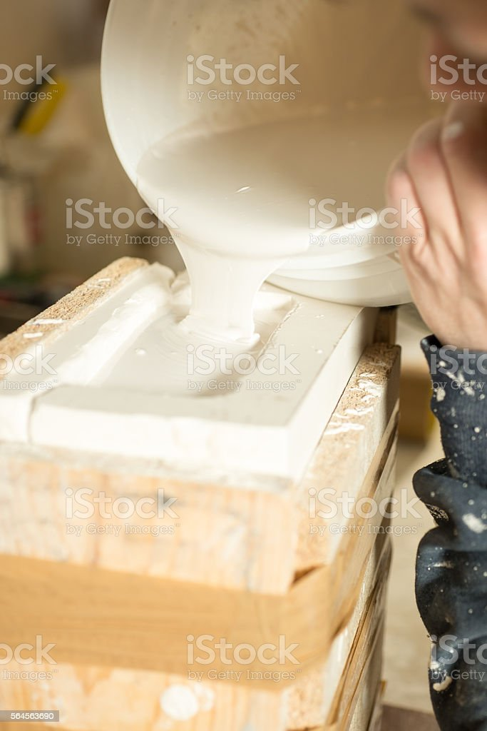 Liquid Plaster Being Poured into Brimming Mold stock photo