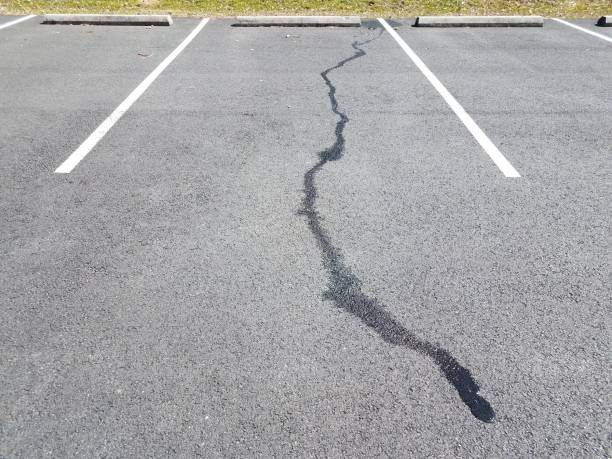 liquid spill on black pavement in parking space stock photo