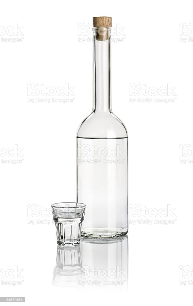 Liquor bottle and beveled shot glass filled with clear liquid stock photo