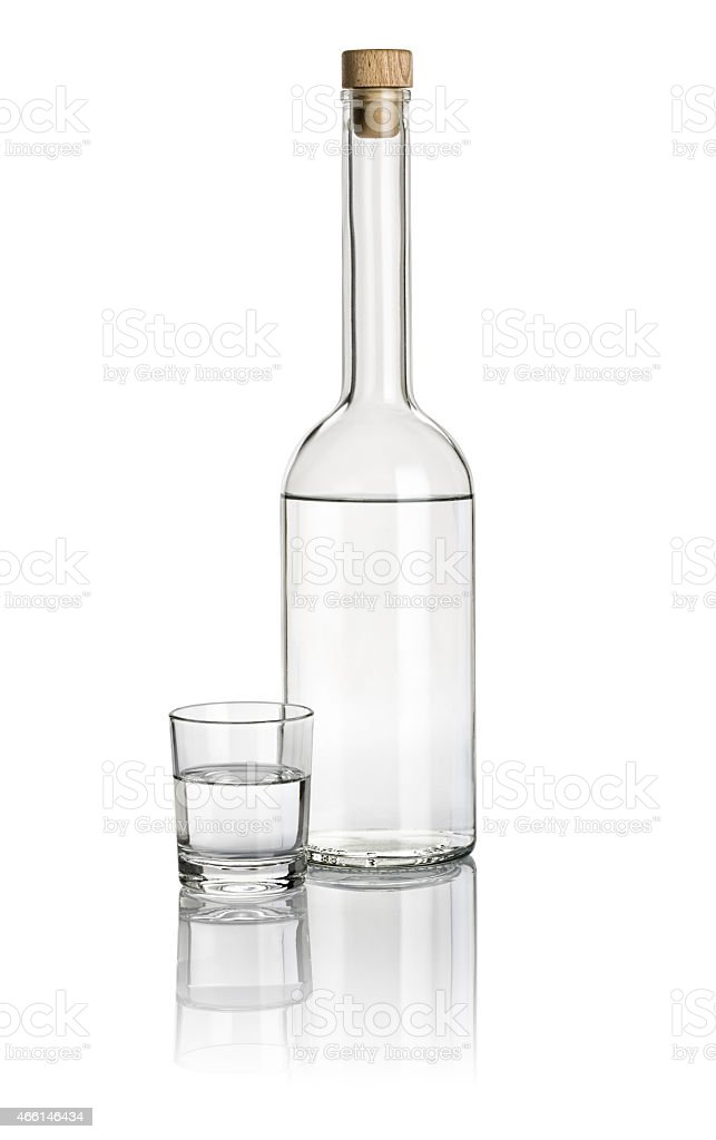 Liquor bottle and drinking glass filled with clear liquid stock photo