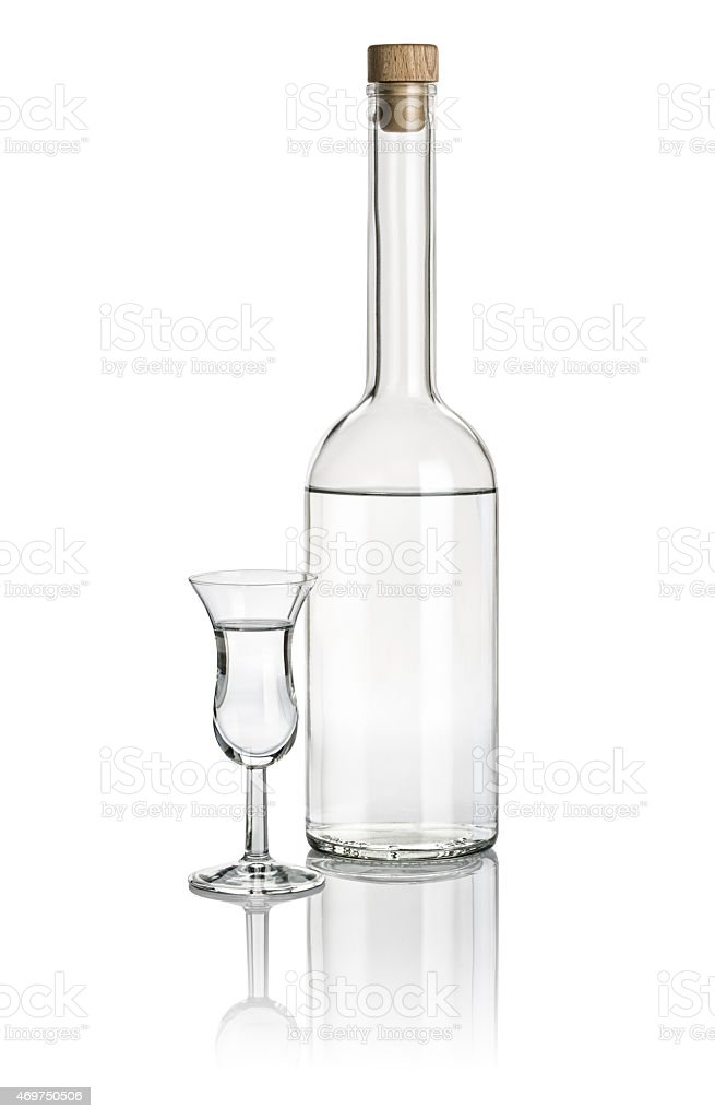 Liquor bottle and high stem glass filled with clear liquid stock photo