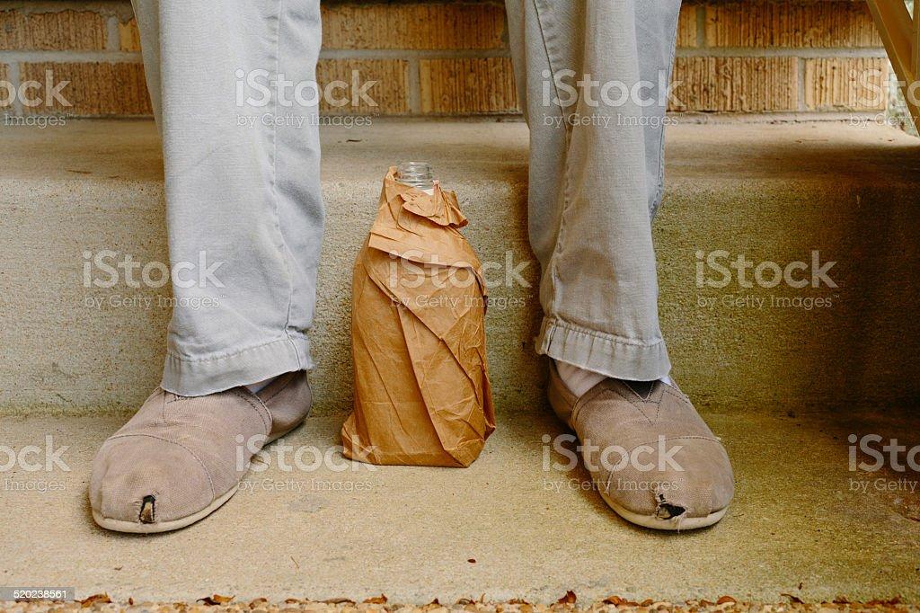 Liquor bottle in paper bag sitting between man's feet stok fotoğrafı