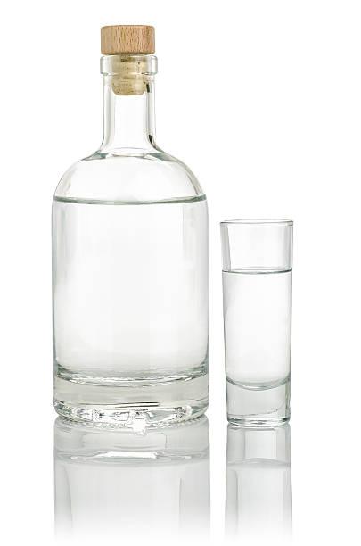 Liquor bottle with a full shot glass Liquor bottle with a full shot glass vodka stock pictures, royalty-free photos & images