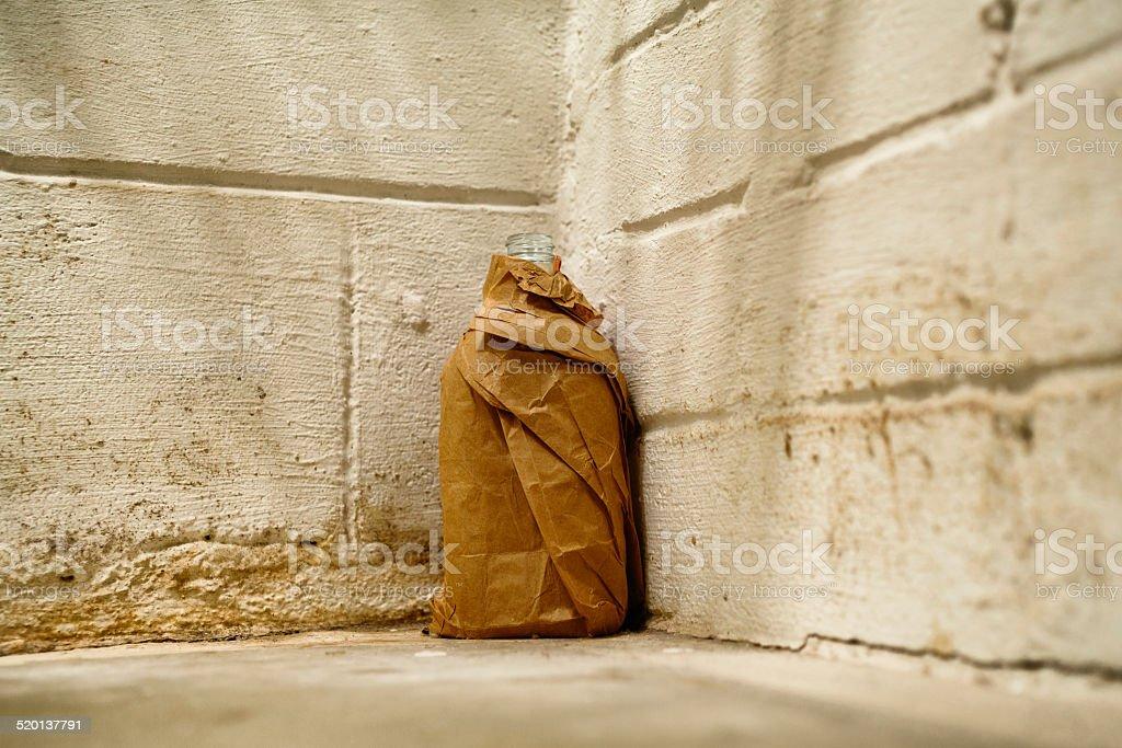 Liquor bottle wrapped in paper bag on abandoned building floor stok fotoğrafı