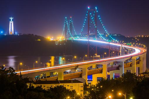 Lisbon 25 de Abril Bridge landmarks illuminated at dusk Portugal