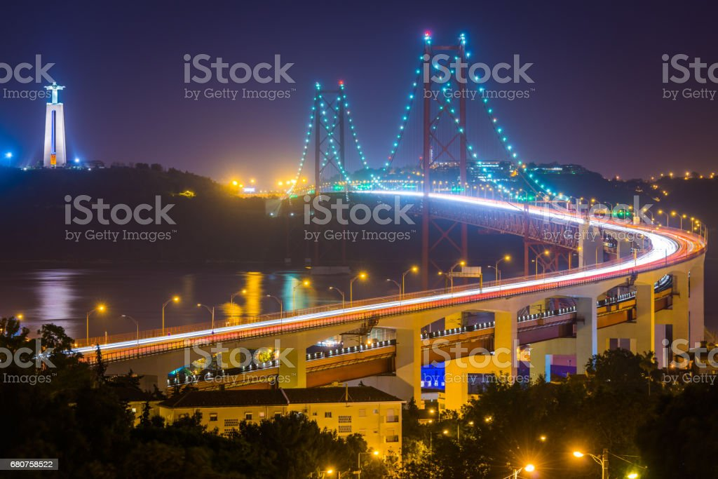 Lisbon 25 de Abril Bridge landmarks illuminated at dusk Portugal stock photo