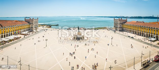 Aerial panorama overlooking the crowds of tourists enjoying the warm sunshine in the Praca do Comercio, the landmark square beside the River Tagus waterfront in the heart of Lisbon, Portugal's vibrant capital city.