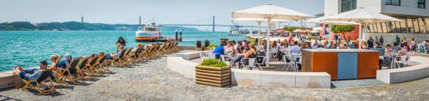 lisbon crowds enjoying sunshine al fresco bar waterfront panorama portugal - esplanada portugal imagens e fotografias de stock