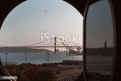 View through opened round illuminator window of an old historic building of an evening Lisbon cityscape with a bridge over the Tejo river in the distance, water, descending airplane