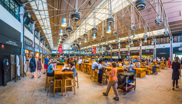 Lisbon Mercado da Riberia Time Out Market restaurants cafes Portugal Crowds of people in the busy Mercado da Riberia Time Out Market enjoying the restaurants, bars and cafes of this redeveloped marketplace in the heart of downtown Lisbon, Portugal's vibrant capital city. market hall stock pictures, royalty-free photos & images
