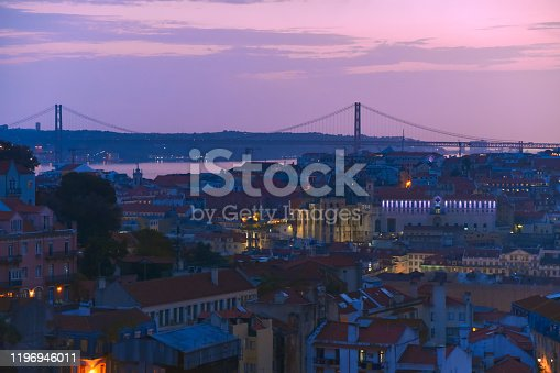 Lisbon panoramic view. Colorful walls of the buildings of Lisbon, with orange roofs and the 25th of April bridge in the background, at sunset. Travel and real estate concept. Lisbon, Portugal. Europe.