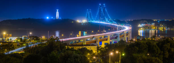 lisbon ponte 25 de abril bridge illuminated night panorama portugal - cristo rei lisboa imagens e fotografias de stock