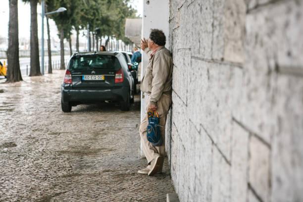 lisbon, portugal 01 may 2018: man near wall on sidewalk waits. pedestrian or tourist on street and expectation or rest or walk - resultados lisboa imagens e fotografias de stock