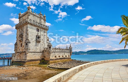 Lisbon, Portugal. Tower Belem at coast of river Tagus. Stones and mussels during low tide. Sunny summer day with blue sky and clouds. Embankment alley with palm tree leaves.