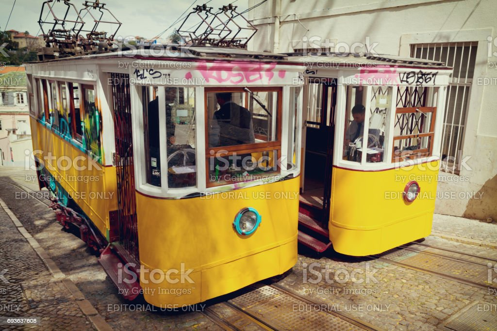 Lisbon, Portugal, 2015 04 17 - two old yellow trams - Ascensor da Gloria standing on the rails stock photo