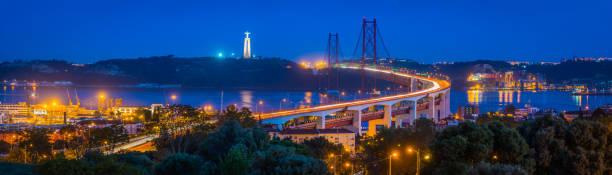 lisbon waterfront 25 de abril bridge illuminated night panorama portugal - cristo rei lisboa imagens e fotografias de stock
