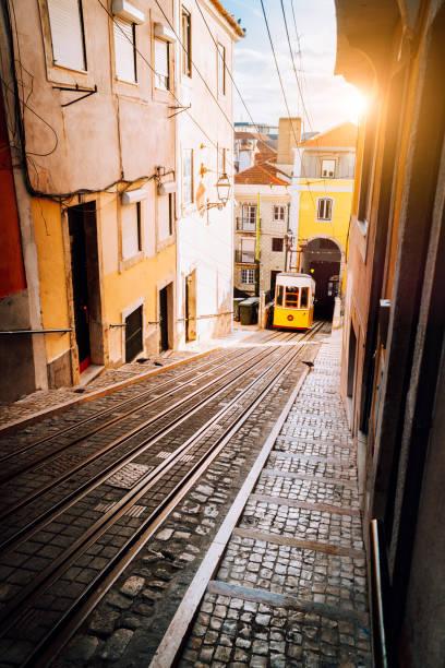 lisbon's gloria yellow funicular in sunset beam light. lisbon, portugal. west side of the avenida da liberdade connects downtown with bairro alto. - people lisbon imagens e fotografias de stock