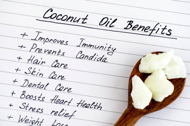 list of coconut oil benefits with wooden spoon with coconut oil. - coconut oil stock pictures, royalty-free photos & images