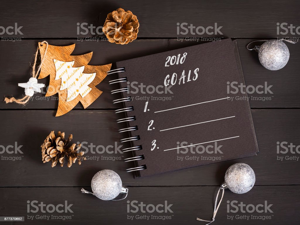 2018 list of goals with a notebook, cones and Christmas decorations on a wooden table. stock photo