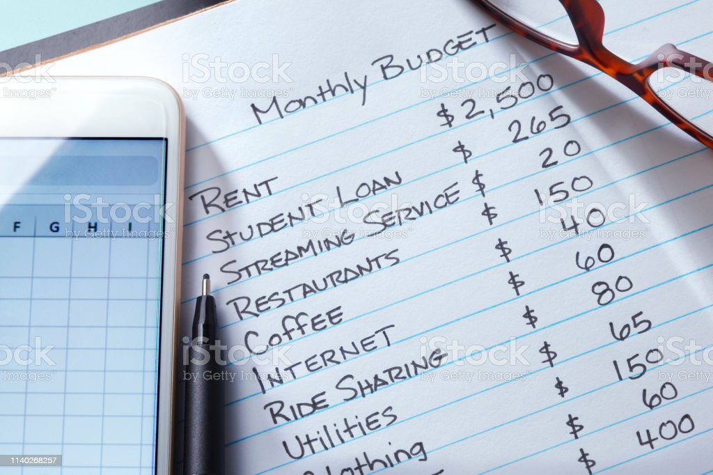 A mobile device and a pen rest on top of a list of monthly expenses...