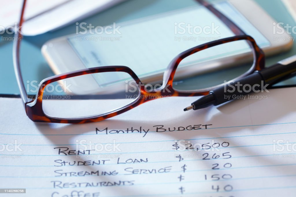 A pair of eyeglasses turned upside down rest on top of a list of...